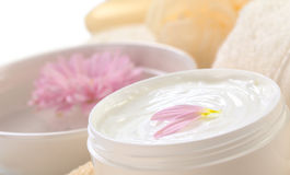 Soft Body, Hand and Face Cream. With pink petals on top in a bathroom/spa setting (Selective Focus, Focus on the horizontal/back petal on the cream Royalty Free Stock Photo
