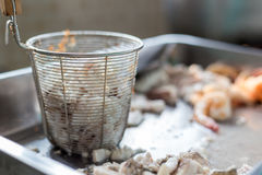 Soft boil seafood. Pieces of fish, squid and shrimp are preparing for make rice congee with sieve for boiling royalty free stock photography