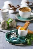 Soft boiled egg. Breakfast with cup of coffee and soft boiled egg, served in green ceramic egg cup with salt, pepper and toasted bread, jug of cream and cotton royalty free stock image