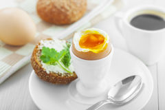 Soft boiled egg breakfast. Perfect soft boiled egg, open bread sandwich with butter and cup of coffee on a table. Traditional food for healthy breakfast Stock Photo
