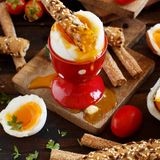 Soft-boiled egg with crisp bread. And tomatoes on a wooden table royalty free stock photos