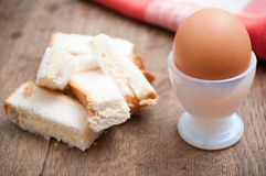 Soft boiled egg in egg cup and served with toast fingers Stock Photos