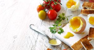 Soft-boiled egg with toasts. And tomatoes on a white wooden table Stock Image