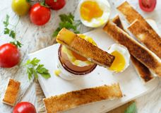 Soft-boiled egg with toasts. And tomatoes on a white wooden table top view Stock Image
