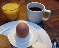 Soft-Boiled Egg. A soft-boiled egg, wholewheat bun, orange juice and coffee make a light breakfast stock photography
