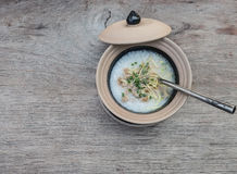 Soft-boiled rice in clay bowl with lid on a wooden tablle Stock Image