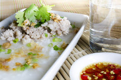 Soft-boiled rice pork with Glass of water and fish sauce Royalty Free Stock Photo