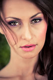Soft breeze in my face. Close-up portrait of a beautiful brunette model with dark brown eyes and the soft breeze blowing hair across her flauless face Royalty Free Stock Photography