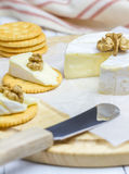 Soft brie cheese with crackers and nuts. On wooden board Stock Photography