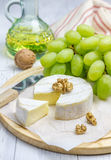 Soft brie cheese with sweet grapes and nuts. Closeup Royalty Free Stock Photo