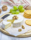 Soft brie cheese with sweet grapes, nuts and crackers. Closeup Stock Photo