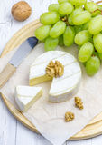 Soft brie cheese with sweet grapes and nuts Royalty Free Stock Photo