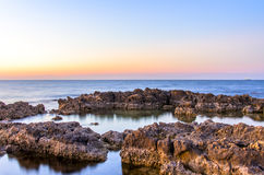 Soft, calm sea sunset. Night falls over the rocky seacost Stock Images