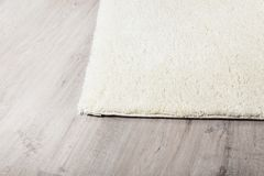 Carpet on laminate flooring. Soft carpet on timber laminate flooring at home stock photography