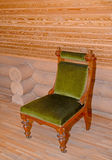 The soft chair with a velvet upholstery stands near a timbered w Royalty Free Stock Photo