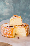 Soft cheese camembert with orange rind, cut off slice, red pepper corns on waxed paper Stock Photo