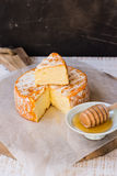 Soft cheese with cut off slice creamy texture, orange rind with mold, French, German,top view, rustic kitchen interior Royalty Free Stock Photography