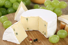 Soft cheese like Camembert or Brie on a wooden board Royalty Free Stock Photos
