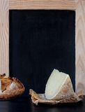 Soft cheese wedge in front of blank old blackboard carte. Stock Image