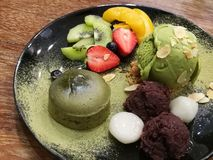 Soft chewy green tea lava cake and green tea ice-cream serving with fresh strawberry, kiwi, peach and sweet red bean, focus-on-for Stock Photos