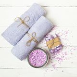 Soft clean towels bath salt a piece of natural soap laid on a light wooden background. Square frame Flat layout. stock photos