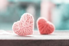 Soft color knitting wool in shape of heart on vintage wooden wit. H bokeh soft light background stock photo