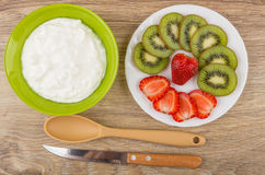 Soft cottage cheese in bowl, slices of kiwi and strawberry Royalty Free Stock Photos