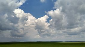 Soft cumulus clouds and green fields, summer landscape. Window royalty free stock image