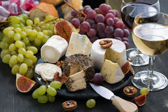 Soft delicacy cheeses and snacks for wine on a dark background Stock Photo