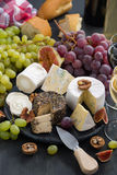 Soft delicacy cheeses and snacks for wine on a dark background Stock Photography