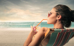 Soft drink at the beach. Young woman drinking a soft drink at the beach royalty free stock photo