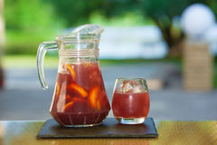 Soft drink and fruit. Jug of non-alcoholic drink and a glass of ice on a table with a blurred background Stock Image