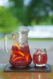 Soft drink and fruit. Jug of non-alcoholic drink and a glass of ice on a table with a blurred background Stock Images