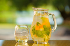 Soft drink and fruit. Jug of non-alcoholic drink and a glass on a table with a blurred background Stock Photography