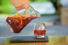 Soft drink and fruit. Mans hand pours jug of non-alcoholic drink in a glass of ice on a table with blurred background Stock Photography