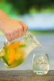 Soft drink and fruit. Mans hand pours jug of non-alcoholic drink in a glass of ice on a table with blurred background Stock Photos