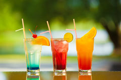 Soft drink and fruit. Three glasses of non-alcoholic drink and fruit on a table with a blurred background Stock Photography