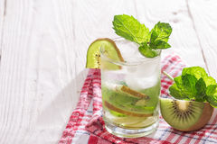 Soft drink with kiwi with ice and mint. Soft drink in a glass on a wooden table Stock Image