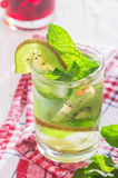 Soft drink with kiwi with ice and mint. Soft drink with ice in a glass on a wooden table Royalty Free Stock Images