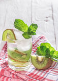 Soft drink with kiwi with ice and mint. On a wooden table Royalty Free Stock Photo