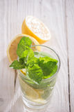 Soft drink with lemon, ice and mint. Soft drink in a glass on a wooden table Stock Images