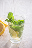 Soft drink with lemon, ice and mint. On a wooden table Royalty Free Stock Image
