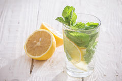 Soft drink with lemon, ice and mint. On a wooden table Stock Photo