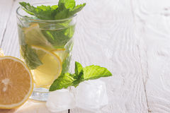 Soft drink with lemon, ice and mint. On a wooden table Stock Image
