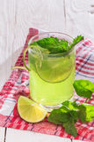Soft drink with lime, ice and mint. Soft drink with ice in a glass on a wooden table Stock Photo