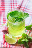 Soft drink with lime, ice and mint. Soft drink with ice in a glass on a wooden table Stock Image