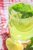 Soft drink with lime, ice and mint. Soft drink with ice in a glass on a wooden table Stock Images
