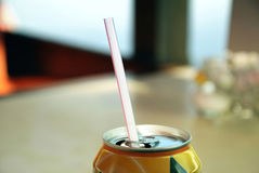 Soft Drink with Pipette. Soft drink in can with pipette, against blurred background in a cafe Royalty Free Stock Image