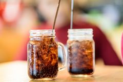 Soft drink. Put ice in a glass, place it on a wooden table in a r royalty free stock images
