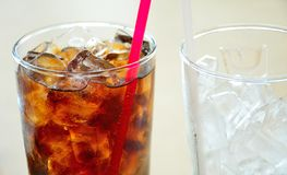 Soft drinks and ice in clear glass. On table Stock Photography